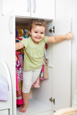 hide and seek: kid girl playing ang hiding inside wardrobe