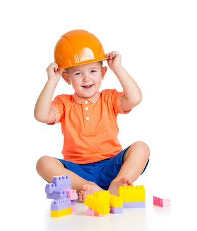 cheerful child boy  playing with building blocks toys over white photo