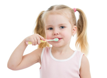 cute child girl brushing teeth isolated on white background photo