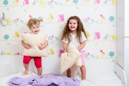 children sisters playing on the bed indoors photo