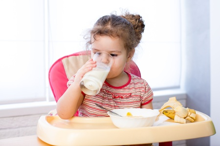 kid girl eating corn flakes with milk photo