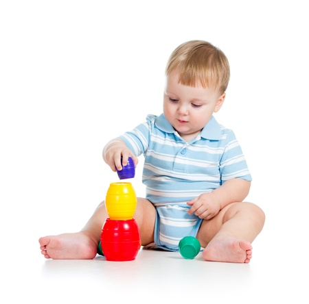 baby boy playing with toys, isolated over white photo