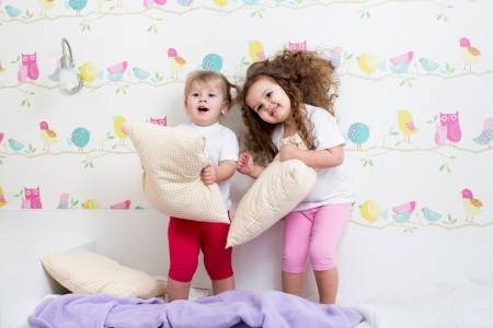 small room: kids sisters playing on the bed indoors Stock Photo