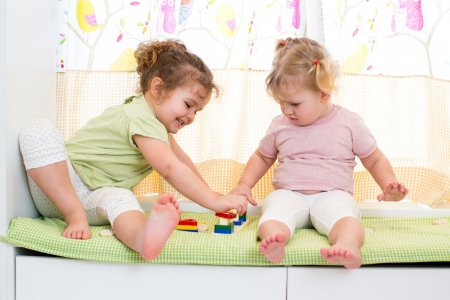 Niños ayudando: niños hermanas juegan juntos en el interior Foto de archivo
