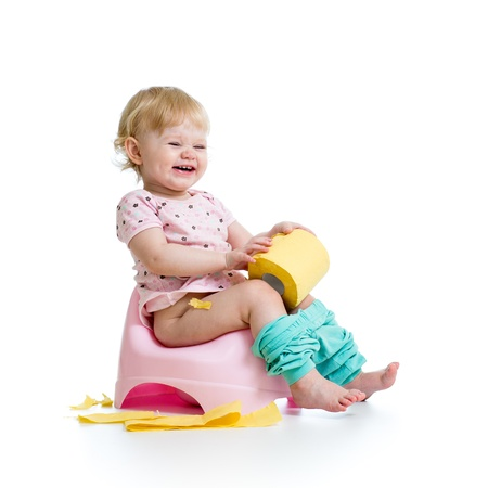 chamber pot: smiling baby sitting on chamber pot with toilet paper roll Stock Photo