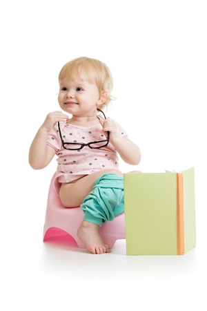 baby girl sitting on chamberpot with book photo