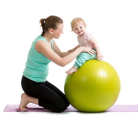 baby with mama: mother with baby having fun with  gymnastic ball