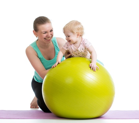 mother doing gymnastics with baby  on fitness ball photo