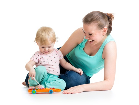 Mother and baby girl having fun with musical toy  Isolated on white background Stock Photo - 19264854