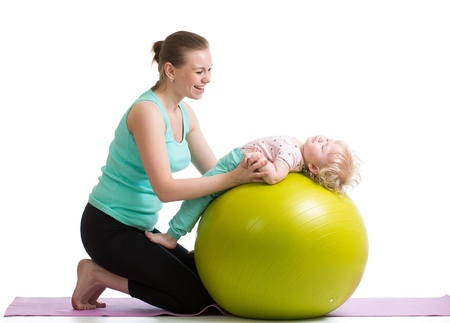 mother with baby having fun with gymnastic ball photo
