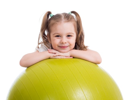 Child girl having fun with gymnastic ball isolated photo