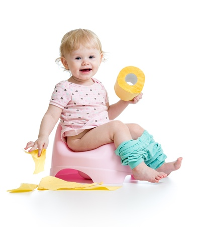smiling baby sitting on chamber pot with toilet paper roll photo