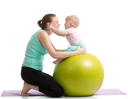 mother and baby having fun with gymnastic ball photo