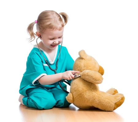 doctor s smock: child with clothes of doctor playing with plush toy Stock Photo