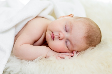 newborn baby girl sleeping on fur bed photo