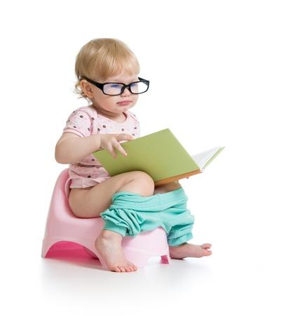 inodoro: ni?a sentada en el orinal con el libro Foto de archivo