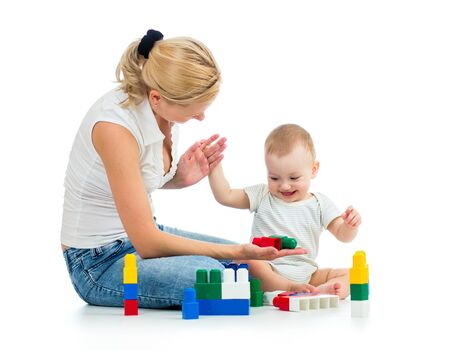 baby boy and mother playing together with construction set toy photo