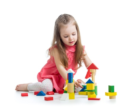 kindergarten toys: child girl playing with block toys over white background