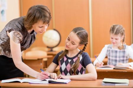 schoolgirl uniform: School kids work at lesson  Teacher controling learning process