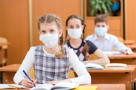 quarantine: school kids with protection mask against flu virus at lesson