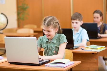 salon de clases: ni?os de la escuela usan la computadora port?til en la lecci?n Foto de archivo
