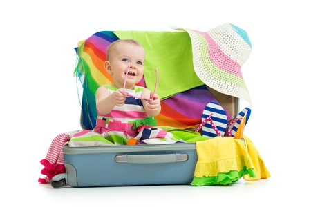 open suitcase: Baby girl sitting in suitcase with  things for vacation travel Stock Photo