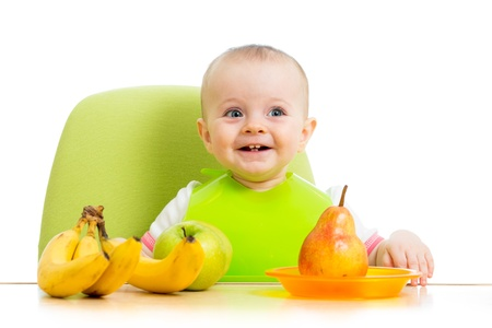 happy baby eating fruits Stock Photo