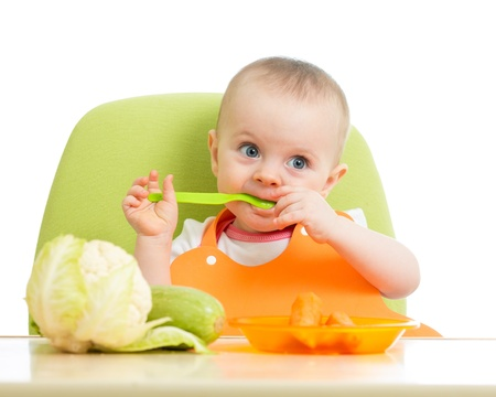 happy baby girl eating vegetables photo
