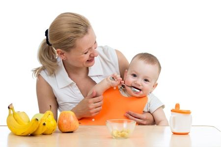 mother spoon feeding baby boy photo