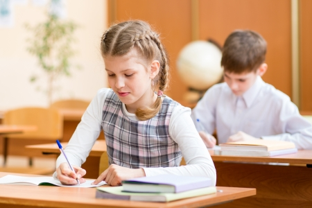children writing: schoolkids writing to copybook at lesson