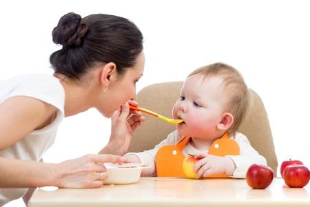 madre y bebe: joven madre cuchara alimenta a su bebé Foto de archivo