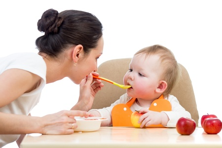 family baby: young mother spoon feeding her baby girl