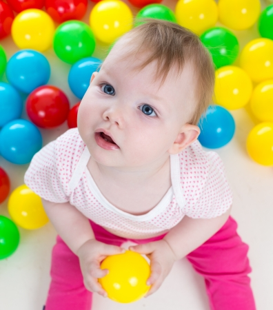 baby girl playing: Top view of baby girl playing with colorful balls Stock Photo