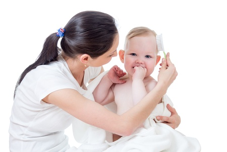 mother combing baby after bathing photo