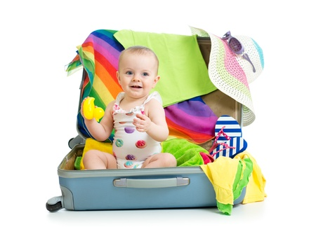 Baby girl sitting in suitcase with  things for vacation travel photo