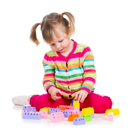child girl playing with construction set over white background photo