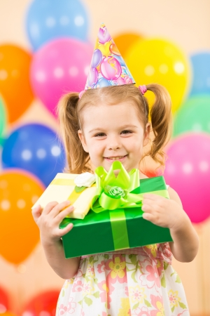 birthday party kids: smiling child girl with gidts on birthday party
