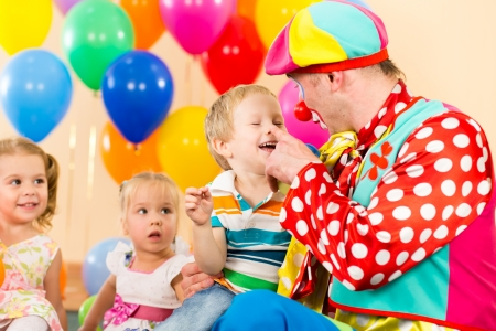 happy kid boy and clown on birthday party photo