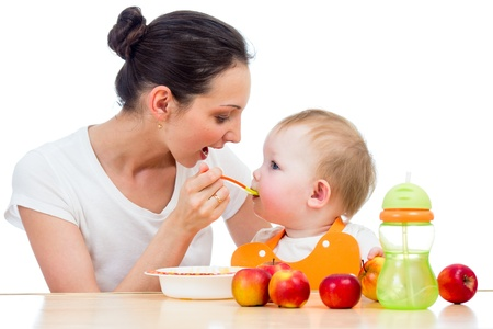 mujer hijos: joven madre cuchara alimenta a su beb? Foto de archivo