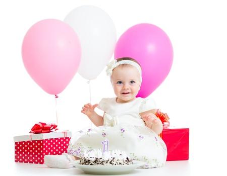 Vrolijke baby meisje met taart, ballonnen en cadeaus. Geïsoleerd op wit.