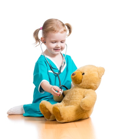 child girl with clothes of doctor playing with plush toy photo