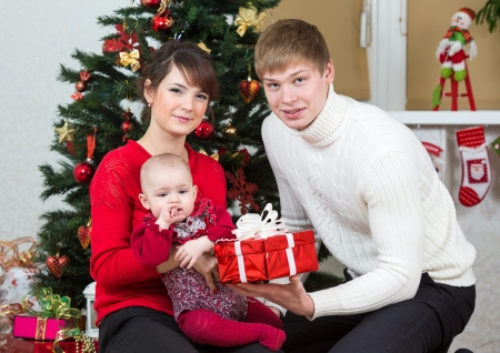 Young family at Christmas tree at home Stock Photo - 20620585