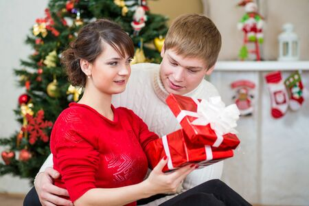 Young couple with gift in front of Christmas tree  at home Stock Photo - 20620584