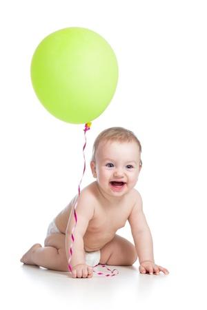 Bebé sonriente con el globo verde en la mano aislados en blanco Foto de archivo