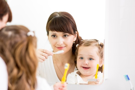 mother instructing kid teeth brushing photo
