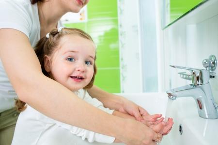 agua grifo: madre lavando las manos del bebé