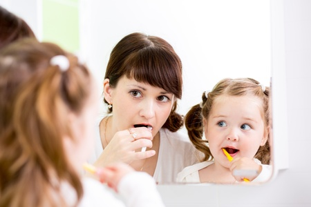 mother teaching kid teeth brushing photo