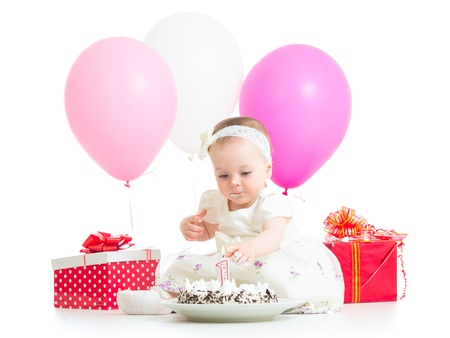 baby girl touching light on birthday cake photo