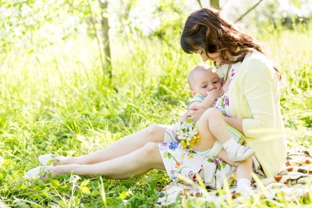 baby feeding: young mother breast feeding her baby outdoors summertime