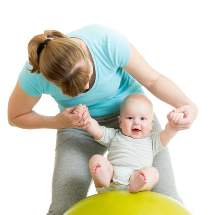 mother playing with baby on gymnastic ball photo